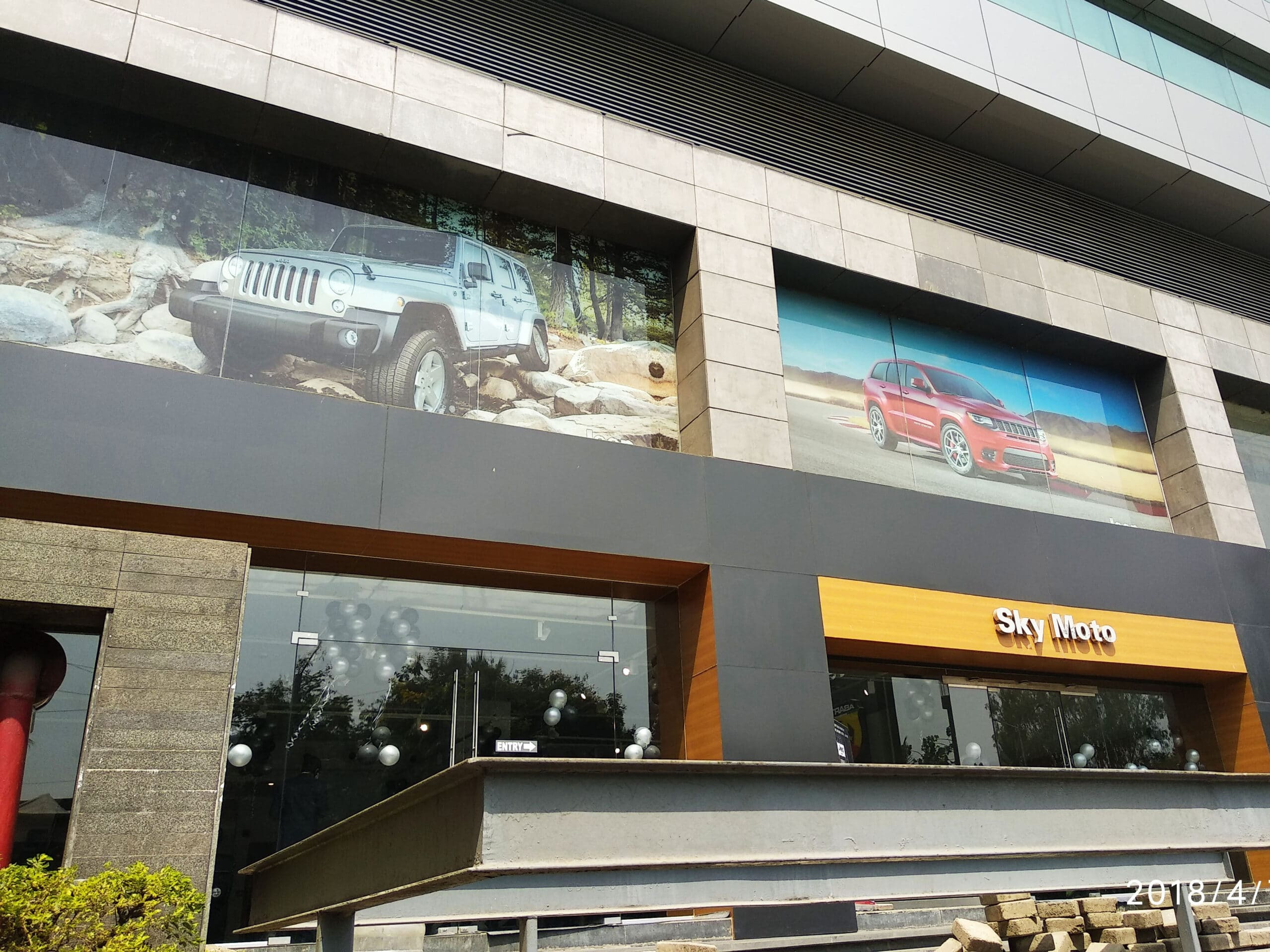 windows of a high rise building used for advertisements using one way vision film by the Jeep company