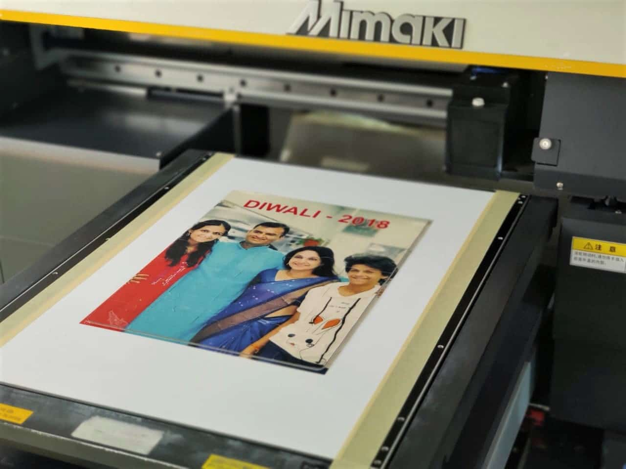Mimaki Ultra Violet flatbed printer printing a family photo on a die cut jigsaw puzzle to create a great personalised gift