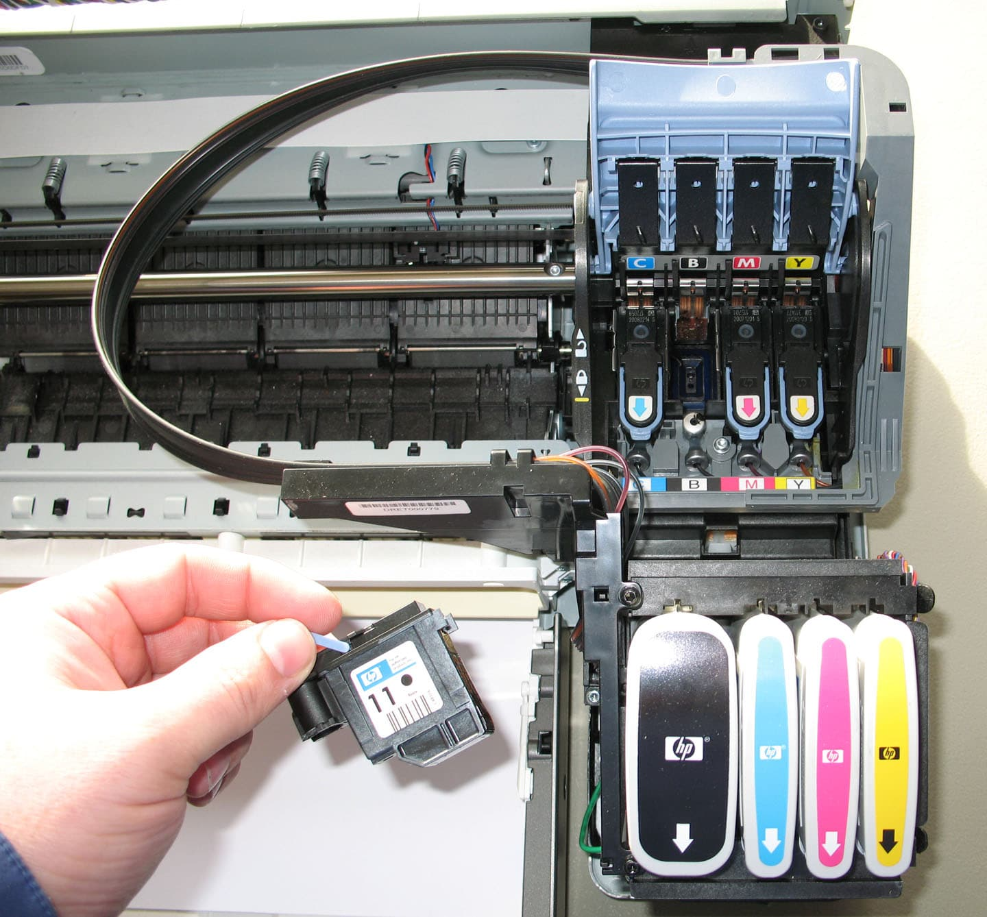 Zoom view of the carriage section of a HP aqueous inkjet printer CMYK ink heads with black head shown removed