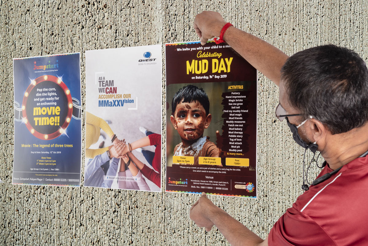 presentation by a red shirted man pasting multiple posters on a wall