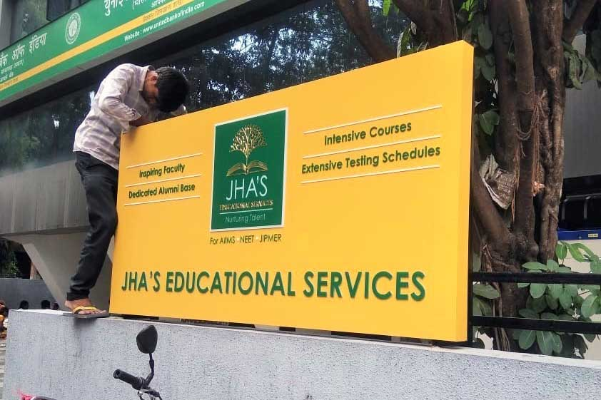 Glow sign board for Jhas Educational Services made of in-cut acrylic letters fixed on an yellow ACP baseboard being fitted on top of a compound wall