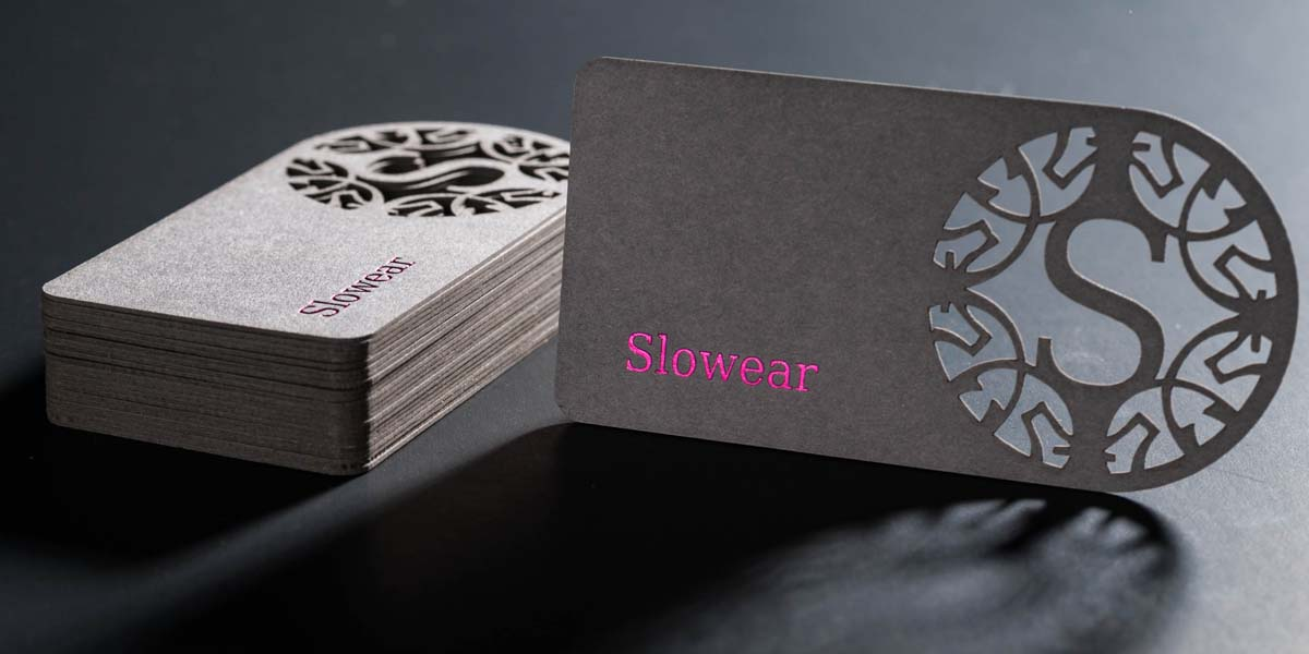stack of laser cut business cards with a company logo cut through thick textured card paper
